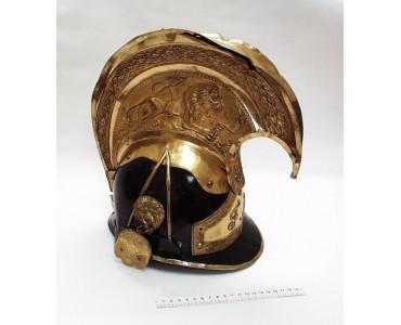 Rakouská důstojnická přilba jezdecká – zvon, z konce 19. století, na temeni vysoký hřeben z mosazného plechu, zdobený reliéfem souboje lva s hadem, po stranách masky lvů, vpředu znak s iniciálami Františka Josefa I.