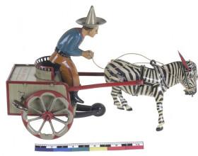 Plechová hračka z první čtvrtiny 20. století – jezdec s vozíkem.
