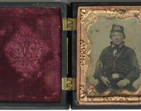 Sedící voják, kolorovaná nestandardní ambrotypie, adjustace typ: Union Cases USA - používáno od roku 1854, uložena v černé plasticky zdobené kazetě, v oválu orel + nápis CONSTITUTION AND THE LAWS
